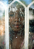 Uganda. Kayunga district. Nnongo. Portrait of a smilling young girl behind a dirty window. © 2004 Didier Ruef