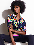Beautiful black woman with in dark blue fashionable shirt with floral design and pants sitting isolated on white background. Image © MaximImages, License at https://www.maximimages.com