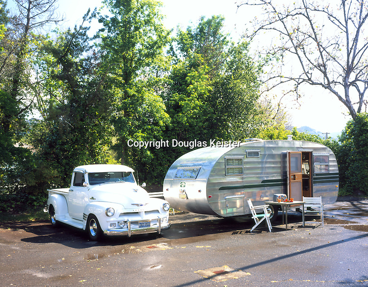 """1954 Traveleze<br />Traveleze can trace its roots to 1931 when southern Californian Kenneth Dixon constructed a trailer from parts of a wrecked 1928 Essex automobile, some scraps of wood framing and some plywood. Dixon, put a """"for sale"""" sign on his creation and it quickly sold. The speed of his first sale convinced Dixon to hang out a shingle as the Traveleze Trailer Company, which sold trailers directly to customers from his Los Angeles factory. During the next few decades Traveleze expanded its production and was well known as an innovator in the industry. In the late 1940's Traveleze introduced the first gas refrigerator and in 1948 they introduce the first production motor home by mounting one of their trailers to a truck chassis. Traveleze weathered the crippling times of the 1970's (oil embargos and soaring interest rates) but eventually went out of business in 1990. In 1998, RV industry giant, Thor Industries resurrected the Traveleze brand.<br /><br />This 1954 Twenty-one and a half foot Traveleze was found, by its current owners, in a field on an Indian reservation near Bishop, California. They had previously owned a smaller Traveleze so were well acquainted with the quality of the trailer. The trailer was a """"park"""" model, so in order to convert it to a true travel trailer they needed to add holding tanks for fresh water and gray/black water and added 12-volt circuitry in addition to the 120-volt wiring. The owners did a lot of the cosmetics themselves, but turned over the wiring and refabrication of some of the exterior panels and doors to Carl Hagen, who they describe as a metal wizard. The paint scheme as well as the decal design is original. The Traveleze trailer is owned by Susan and Dan Cutright. The 1955 Chevrolet First Series Advanced Design Pickup is owned by Mike and Debbie Smith. Photographed at the Silver Social, Calistoga, California."""