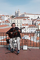 Lisbon, Portugal. 23.03.2015. A Fado singer entertains tourists at a viewpoint in the Alfama district. The Monastery of São Vicente de Fora is in the background.  © Jane Hobson.