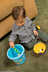 16 month old toddler boy sitting dropping toy animal into bucket