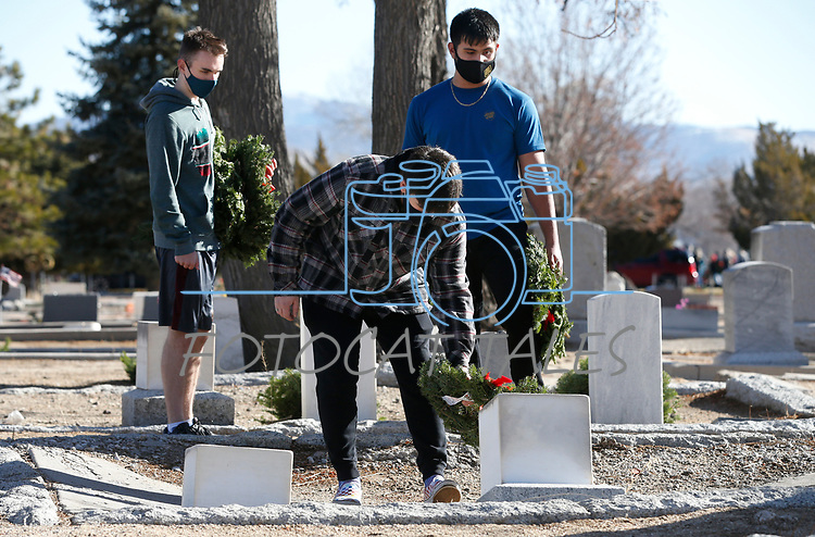 As part of National Wreaths Across America Day, volunteers, from left, Zachary Homola, Christopher Vaughan and Marco Barraza place wreaths on the graves of veterans at the Lone Mountain Cemetery, in Carson City, Nev., on Saturday, Dec. 19, 2020. The program honors veterans at more than 2100 cemeteries around the world. <br /> Photo by Cathleen Allison/Nevada Momentum Fueled by RAD