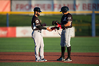 Salem-Keizer Volcanoes manager Hector Borg (13) takes batting gear from Diego Rincones (19) during a Northwest League game against the Hillsboro Hops at Ron Tonkin Field on September 1, 2018 in Hillsboro, Oregon. The Salem-Keizer Volcanoes defeated the Hillsboro Hops by a score of 3-1. (Zachary Lucy/Four Seam Images)