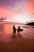Silhouette of surfer couple at sunset at Waimea Bay Beach Park, Oahu