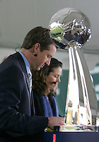 ESPN broadcasters Rob Stone and Julie Foudy check their notes behind the Alan I. Rothenberg trophy. The Houston Dynamo defeated the New England Revolution 2-1 in the finals of the MLS Cup at RFK Memorial Stadium in Washington, D. C., on November 18, 2007.