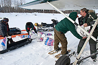 Volunteer pilot Danny Davidson unloads his plane with musher's food bags on the Yukon River at the Eagle Island checkpoint during Iditarod 2009