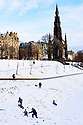 A family enjoys the first snowfall of the first Covid Winter, in front of the Scott Memorial, Princes Street Gardens, Edinburgh. Edinburgh has been placed in Tier 4 restrictions due to the Covid-19 pandemic.