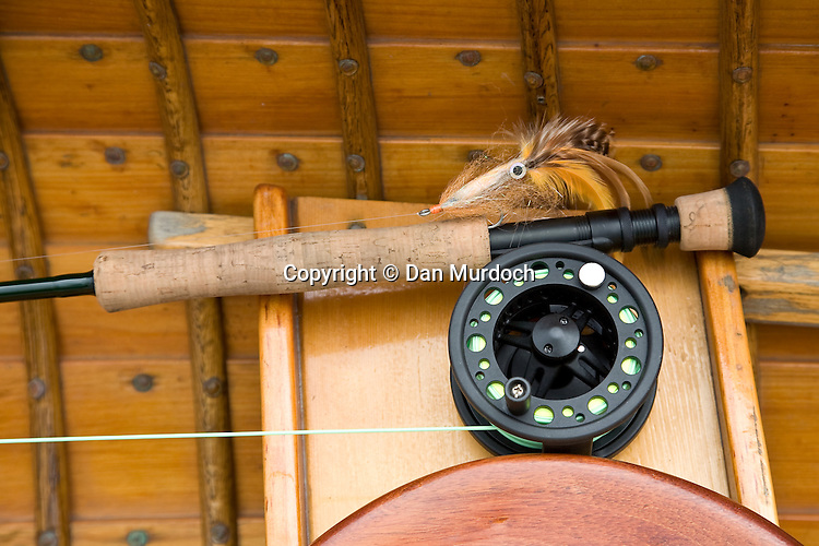flyfishing rod, reel, and fly in wooden kayak