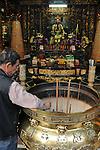 Bao-jhong Yi-min Temple, Kaohsiung -- Temple custodian cleaning the joss stick brazier of incense ash.