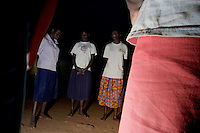 An early morning prayer and fellowship before the day begins. NoahÕs Ark Shelter. The shelter  is one of the few places children, known as Night Commuters, can find protection every  night to avoid being abducted by the Lords Resistance Army (LRA) in Northern Uganda. The LRA is primarily made up of abducted youth. Night Commuters find much more than safety in the compounds, they also find friendships, activity and fellowship. Tens of thousands of children, on average, make this exodus every evening. The war in Northern Uganda has been transpiring for two decades. Gulu, Gulu District, Uganda, Africa. December 2005 © Stephen Blake Farrington
