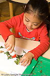 preschool 2-3 year olds art activitiy nature science observation girl gluing bits of leaves to paper