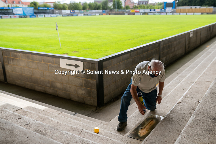 Pictured: Volunteer maintenance worker Ray Neal sprays the stencil of an arrow on the floor to comply with social distancing measures during preparations ahead of crowds being welcomed back into sporting events at The Raymond McEnhill Stadium in Salisbury, Wilts.<br /> <br /> Inline with the governments easing of lockdown restrictions, Salisbury Football Club are preparaing to welcome back 30% of their fans as of this Monday, August 31st. <br /> <br /> Salisbury FC play in Southern League Premier Division South, or step 3 of the non-league football ladder. <br /> <br /> © Jordan Pettitt/Solent News & Photo Agency<br /> UK +44 (0) 2380 458800