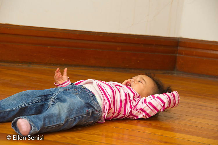 MR / Schenectady, NY. Infant (girl, 12 months, African American & Caucasian) lies on the floor crying, having a temper tantrum. MR: Dal4. ID: AL-HD. © Ellen B. Senisi