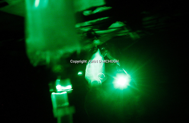 """IVs are seen under a green light as a US Medevac helicopter from the 101st Aviation Regiment flies on a rescue mission at night to collect 2 American soldiers, wounded in an Improvised Explosive Deviece (IED) attack, and take them Forward Operating Base Orgun-E in Paktika province, Afghanistan, 21 July, 2008. Also known by their call sign """"Dust Off"""","""" the Medevac pilots, crew and medics are ready to fly at a moments notice, picking up Coalition soldiers as well as Afghans that require help.(John D McHugh)"""