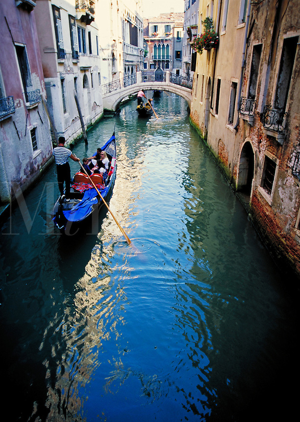A gondolier navigating the narrow canals of Venice, Italy. waterways, boat, cityscape, boats, transportation. Venice, Italy.