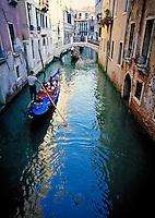 A gondolier navigating the narrow canals of Venice, Italy. waterways, boat, cityscape, boats, transportation. Venice, Italy.