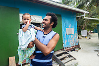 Frank Fiapati, 30, plays with his youngest child outside their home in Funafuti, Tuvalu. Located in the South West Pacific Ocean, Tuvalu is the world's 4th smallest country and is one of the most vulnerable to climate change impacts including sea level rise, drought and extreme weather events. Tuvalu - March, 2019.