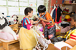 Education Preschool 4-5 year olds pretend play boy using stethoscope on girl in dressup costume boy in fire fighter jacket looking on