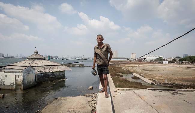 13 August 2019, Jakarta, Indonesia: Local resident Iwan stands on the protective seawall barrier keeping the ocean at bay at Muara Baru, North Jakarta. Built by Governor (now President) Joko Widodo it was constructed to prevent further encroachment by the ocean into the settlements in North Jakarta which is sinking at a rate faster than anywhere else in the world. Residents speak of the flooding  that would drive them to higher ground washing away all in its path. Residents now say the land is dry and usable but it is an ongoing crisis for Indonesia. Picture by Graham Crouch/The Telegraph