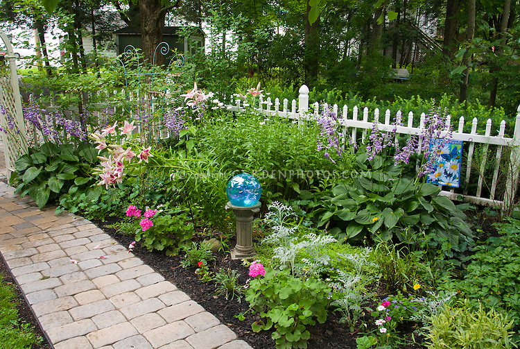 Shade garden with hostas, lilies, gazing ball, white picket fence, pathway