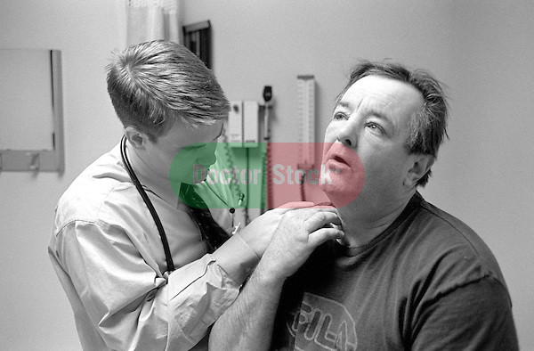 Young male doctor examining neck of middle age male patient in examination room