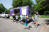 Children get lunch from the Fayetteville Public School's food truck. Wednesday July 14, 2021 at the Yvonne Richardson Center in Fayetteville. Children can get lunch at the truck Monday through Thursday with a sack lunch for Friday and a weekend package with food to last until Monday. The food truck stops at the Donald W. Reynolds Boys and Girls Club as well. Visit nwaonline.com/21000715Daily/ and nwadg.com/photo. (NWA Democrat-Gazette/J.T. Wampler)