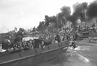 Australian troops storm ashore in the first assault wave to hit Balikpapan on the southeast coast of oil-rich Borneo.  Coast Guard Combat Photographer James L. Lonergan stands in the landing craft.  July 1945.  Gerald C. Anker.  (Coast Guard)<br /> Exact Date Shot Unknown<br /> NARA FILE #:  026-G-4718<br /> WAR & CONFLICT BOOK #:  1171