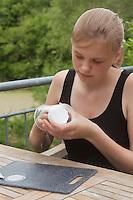 Mädchen, Kind bastelt eine Becherlupe, Beobachtungsgefäß aus 2 durchsichtigen Plastikbecher, einem Stück Styropor und Frischhaltefolie. 4. Schritt: das kreisförmige Styroporstück wird in den aufgeschnittenen Plastikbecher gesteckt