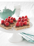 Squares of toast topped with hazelnut-chocolate spread and raspberries. Teapot in background