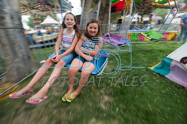 (From Left) Gillian Ladiges,10, and Peyton Ladiges, 9, laugh while riding a ride during the NV150 Fair at Fuji Park in Carson City, Nev., on Sunday, August 3, 2014.<br /> (Photo By Kevin Clifford)