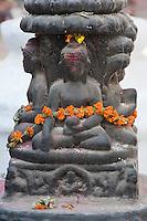 Bodhnath, Nepal.  A Statue of the Buddha adjacent to the Buddhist Stupa of Bodhnath.