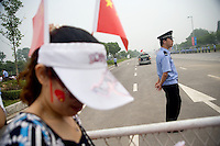 A policeman keeps the road clear and watches the crowd of spectators during the Nanjing, China, leg of the 2008 Olympic Torch Relay.