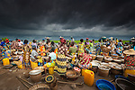 In the tiny country of Benin, West Africa, large, freshwater lakes provide a bountiful harvest for local fishermen and open-air markets. This marketplace presents a colorful foreground as a storm builds on the distant horizon. Moments later, the skies opened in a tremendous downpour, producing a frenzied search for shelter.