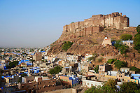 The Blue City and Fort of Jodhpur Rajasthan India. J o d h p u r   J o d h p u r  i s   t h e   s e c o n d   l a r g e s t   c i t y   i n   t h e   I n d i a n   s t a t e   o f   R a j a s t h a n .   I t   w a s   f o r m e r l y   t h e   s e a t   o f   a   p r i n c e l y   s t a t e   o f   t h e   s a m e   n a m e ,   i t   i s   t h e   c a p i t a l   o f   t h e   k i n g d o m   k n o w n   a s   M a r w a r .   J o d h p u r   i s   a   p o p u l a r   t o u r i s t   d e s t i n a t i o n ,   f e a t u r i n g   m a n y   p a l a c e s ,   f o r t s   a n d   t e m p l e s ,   s e t   i n   t h e   s t a r k   l a n d s c a p e   o f   t h e   T h a r   d e s e r t . . T h e   c i t y   i s   k n o w n   a s   t h e   S u n   C i t y   f o r   t h e   b r i g h t ,   s u n n y   w e a t h e r   i t   e n j o y s   a l l   y e a r .   I t   i s   a l s o   r e f e r r e d   a s   t h e   B l u e   C i t y   d u e   t o   t h e   i n d i g o   t i n g e   o f   t h e   w h i t e w a s h e d   h o u s e s   a r o u n d   t h e   M e h r a n g a r h   F o r t .