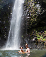 A young couple soak in the sun and water at Uluwehi Falls, Kaua'i.