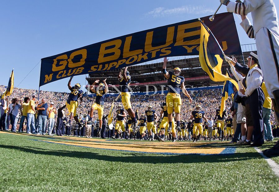 "11 October 2008: Michigan football players take the field, running under and touching the ""Go Blue"" banner, before an NCAA college football game between the Michigan Wolverines and Toledo, at Michigan Stadium in Ann Arbor, Michigan."