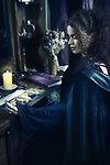 Portrait of a Beautiful mysterious woman fortune teller reading Taror cards at a table, Tarot card reader, devination artistic concept Image © MaximImages, License at https://www.maximimages.com