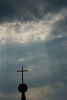A cross is silhouetted against the sun's ray shining through clouds over the cemetery at St. Joseph's Church in Somerset, Ohio. The church is the oldest Catholic church in Ohio.<br />