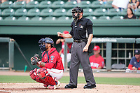 Umpire Jose Lozada works a game between the Hickory Crawdads and the Greenville Drive on Friday, June 18, 2021, at Fluor Field at the West End in Greenville, South Carolina. The catcher is Alan Marrero (1). (Tom Priddy/Four Seam Images)