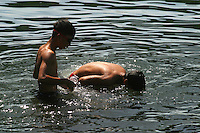 Boys scope the shallows for fish under the boardwalk in the polluted waters of Manila Bay by Rizal Park, the largest park in Manila, Philippines named after national hero Jose Rizal. 2 December 2004