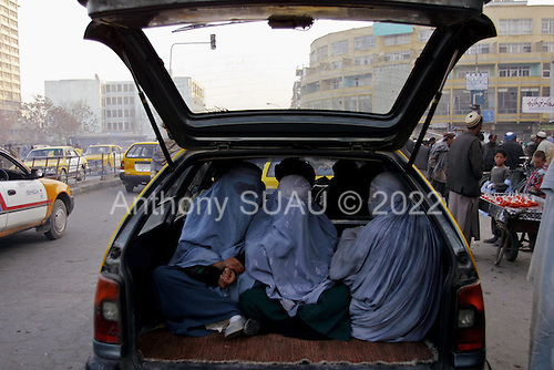 Kabul, Afghanistan<br /> November 2001<br /> <br /> A women travel into the boot of a car like luggage.