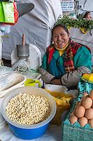 Peru, Cusco, San Pedro Market.  Woman Selling Eggs, Beans, and Melon.