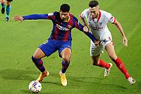 4th October 2020; Camp Nou, Barcelona, Catalonia, Spain; La Liga Football, Barcelona versus Sevilla; Araujo of Barcelona holds off the challenge from Ocampos of Sevilla