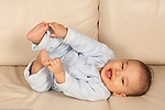 6 month old baby boy lying on back full length grabbing feet Asian American Chinese