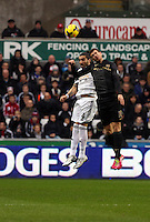 Wednesday, 01 January 2014<br /> Pictured L-R: Chico Flores battles for a header against Edin Dzeko of Manchester City. <br /> Re: Barclay's Premier League, Swansea City FC v Manchester City at the Liberty Stadium, south Wales.