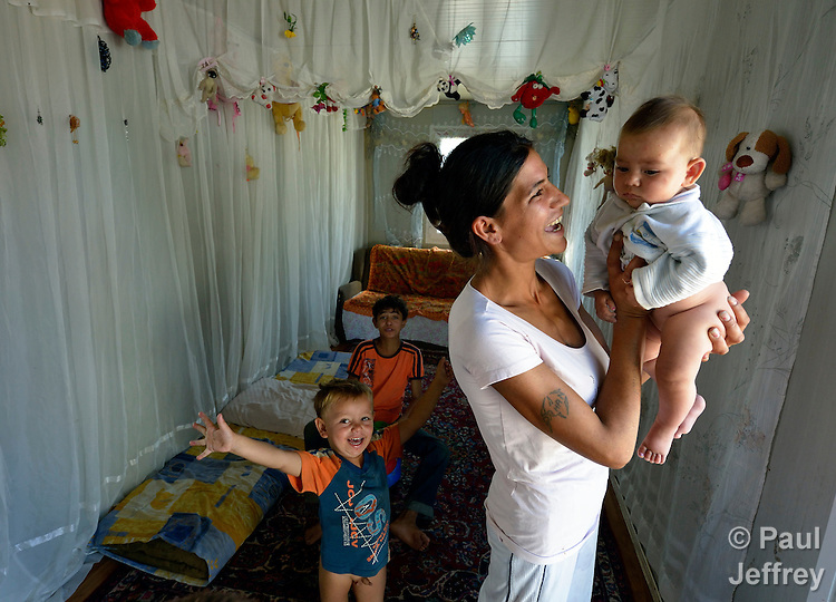 A Roma woman holds her baby inside a shipping container that has been converted into a house in Makis, a village outside of Belgrade, Serbia. These Roma families were evicted from an urban squatter settlement in 2012 to make way for construction of new apartments and office buildings. The shipping containers they now call home, which were provided at no cost by local authorities, are far from the city center.