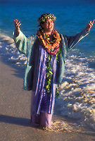 A kumu (teacher) wearing leis chants by the shoreline of a beach on Oahu.