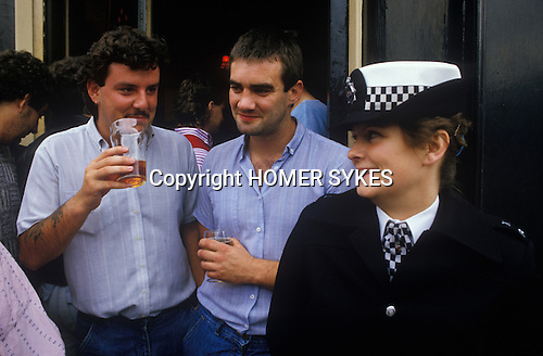 Two male Chelsea football fans having a pint before the game, flirting with an attractive female police woman. London. UK 1980s