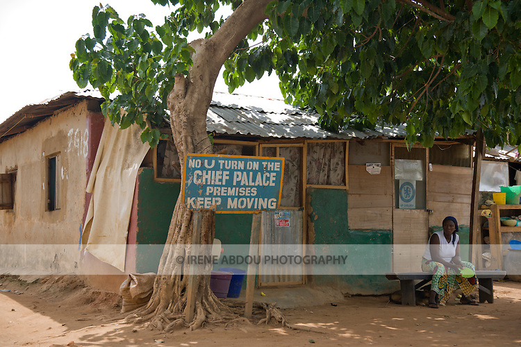 """A woman lounges in front of this Chief's Palace in the Durumi area of Abuja, Nigeria.  The sign reads, """"No U Turn on the Chief Palace Premises Keep Moving."""""""