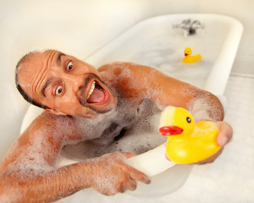 Man in bath tub, with bubbles. Rubber duck on head, rubber duck behind him in tub.